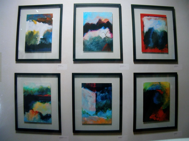 wall of six small painitngs at gallery 100, in see-through frames