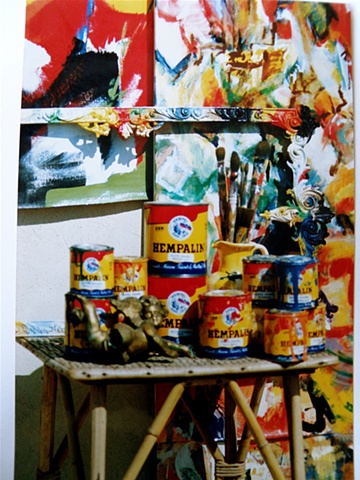 several paint cans, studio angel, brushes, mirror frame and paintings