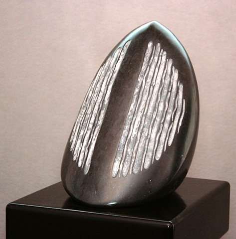 This is a comtemporary stone sculpture of a very large black  seed by Denis A. Yanashot.