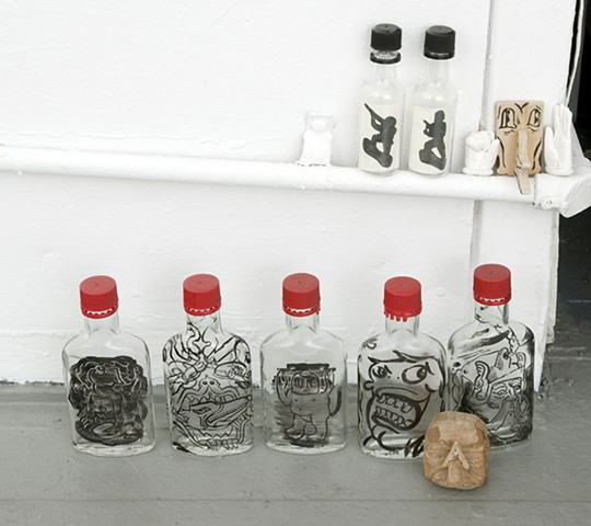 bottles with drawings inside or drawn on using sumi ink.