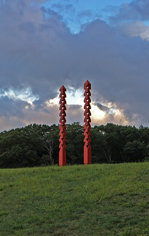 External Link - a pair of carved rhythmic obelisks frame views, imply an axis, and become a gate