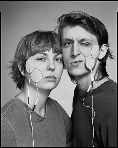 "A photograph of a couple receiving an electric current through their faces from the series ""Sing the Body Electric"""