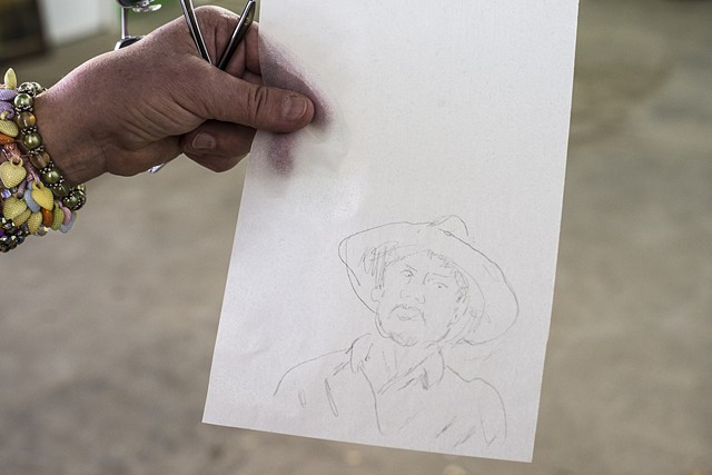 A digital photograph by Stephen Takacs that documents a participants portrait drawing of a man with a hat made with the Victrola Obscura at 400 West Rich
