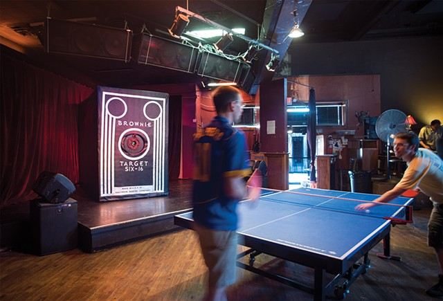 A digital photography of a gigantic Brownie camera and two ping pong players at Ace of Cups for the Brownie In Motion Project by Columbus, Ohio based photographer Stephen Takacs.