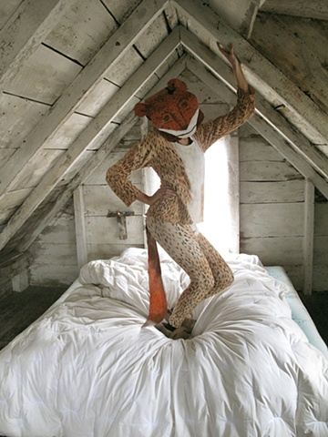 From the project The Weasel Problem, a collaboration project by Zehra Khan & Tim Winn, For You, #photograph #dune shack #Provincetown #CapeCodNationalSeashore #bed #weasel #costume #performer #longjohns #Zehra Khan #Tim Winn #costume