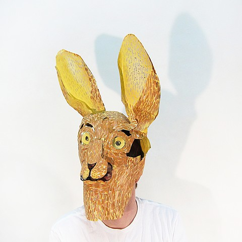 Male Rabbit is a paper mask created by Zehra Khan. The masks are often made from repurposed paper from other art projects.  As the two-dimensional paper is bent, cut and glued into three-dimensional form, it gains rigidity but retains the inherent fragil