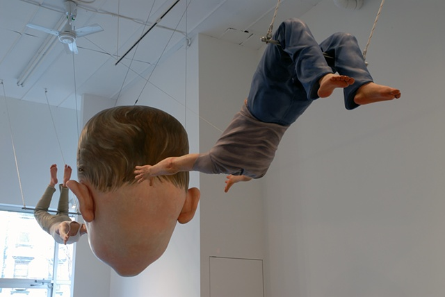 Polychrome figurative sculpture of a life-size headless woman and man tossing a huge child's head between them on a trapeze