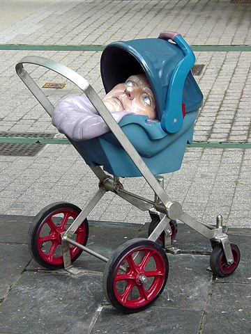 stainless steel stroller holding a car seat which contains an oversized adult head