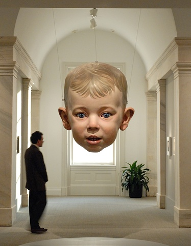 Large figurative polychrome sculpture of a child's head suspended from the ceiling, installed at the National Portrait Gallery in DC