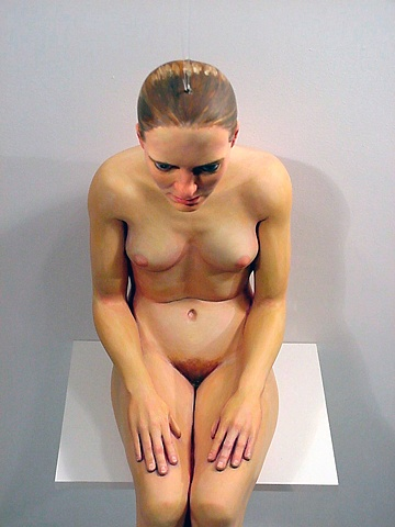 figurative polychrome sculpture which uses perspective to put a head on a headless bosy, smaller than life-size sitting on a shelf
