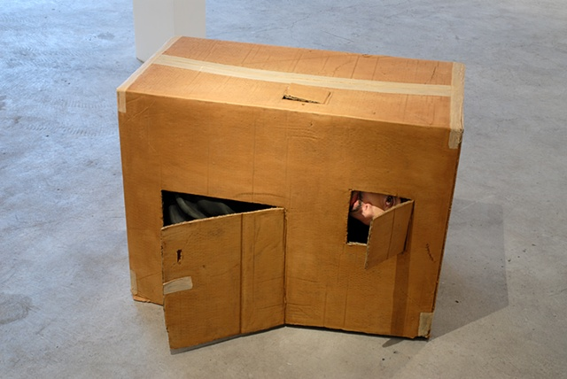 Figurative polychrome sculpture of adult man stuffed inside a cardboard box or child's playhouse