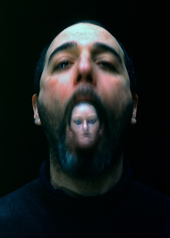 Blurry photograph of a man with a small sculpted, painted woman's head in his mouth