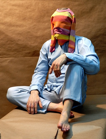 cast ultracal figurative polychrome sculpture of a man with a small child's shirt over his head