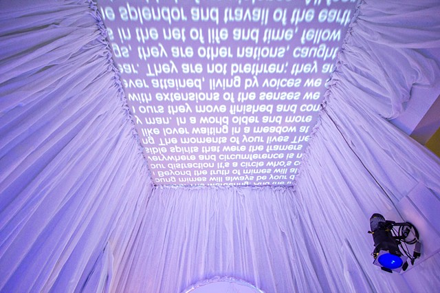 Installation view of backwards scrolling text, projected onto ceiling