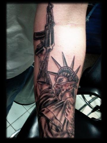 statue of liberty with gun tattoo by tatupaul.com