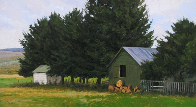 Landscape with spruce trees, green woodshed, firewood