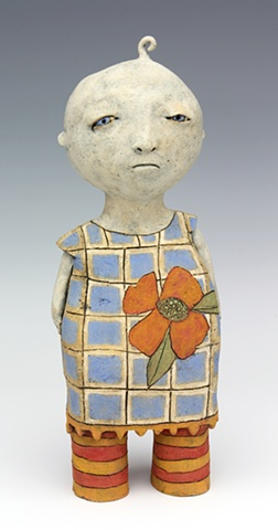 ceramic figure of a baby girl in a dress with a big flower