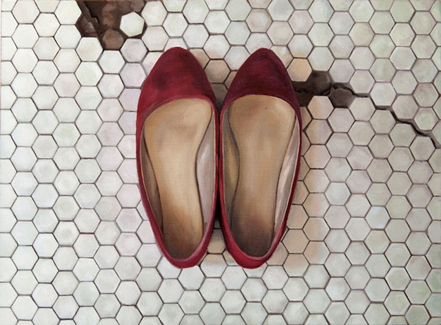 Worn red shoes on the bathroom floor