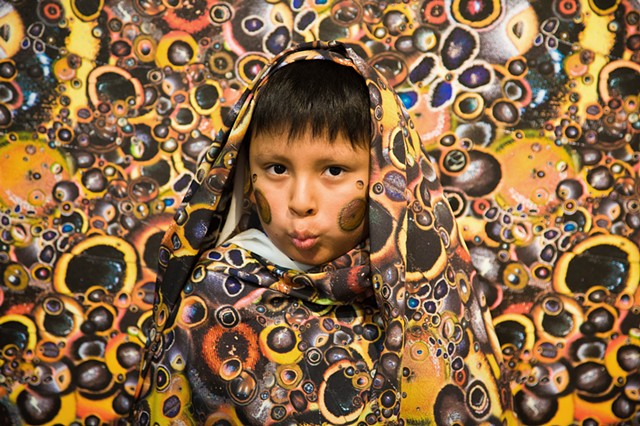 The artist photographed local kids using the 'camouflaging' temporary face tattoos