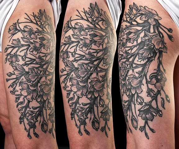 flowers on vines black and grey thigh tattoo