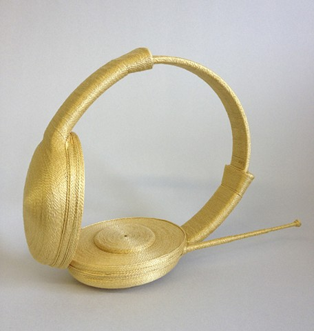 Headphones wrapped in gold thread.
