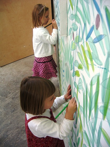 "little girls drawing on the wall of an olive grove sanctuary theatrical installation environment by Eugenia Mitsanas for ""Olive Grove Project"" at Workspace Ltd."
