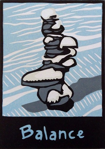 a reduction linocut of stacked stones with snow on top of the stones by Leslie Moore of PenPets