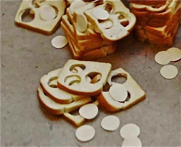 Stacks of white bread with 3 circles each removed and thrown around the stacks.