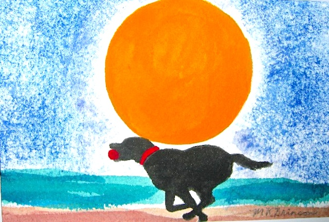 A black lab runs with a red ball on the beach in front of a big orange sun at sunset.