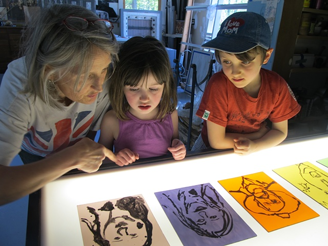 children looking at stained glass portraits they painted in stained glass