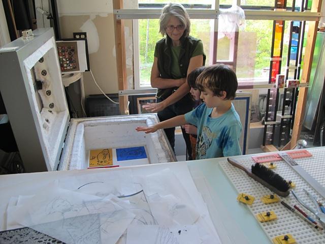 children feeling heat from stained glass kiln