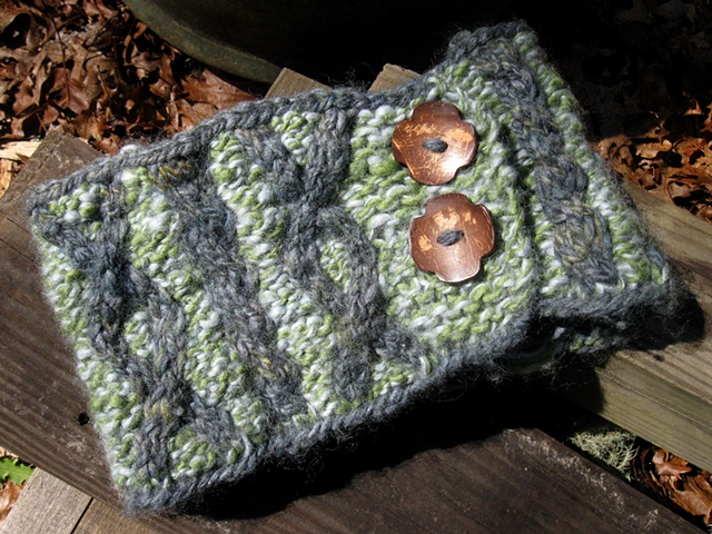 a cable knit neckwarmer with buttons made of 2 colors of handspun hand dyed wool yarn