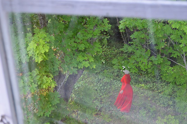 photograph of woman red dress green forrest window by Robyn LeRoy-Evans