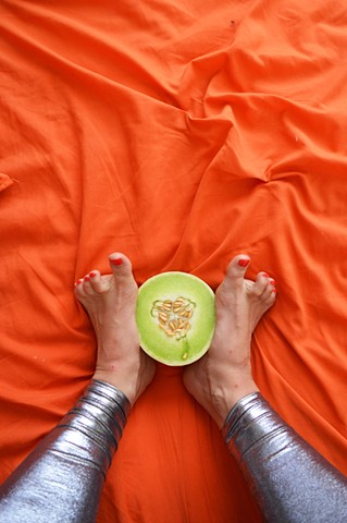 photograph of woman feet legs toes honeydew melon food silver leggings fetish orange bed by Robyn LeRoy-Evans