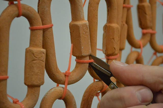 %Access Restricted% is a labor-intensive terra cotta and cable tie fence.