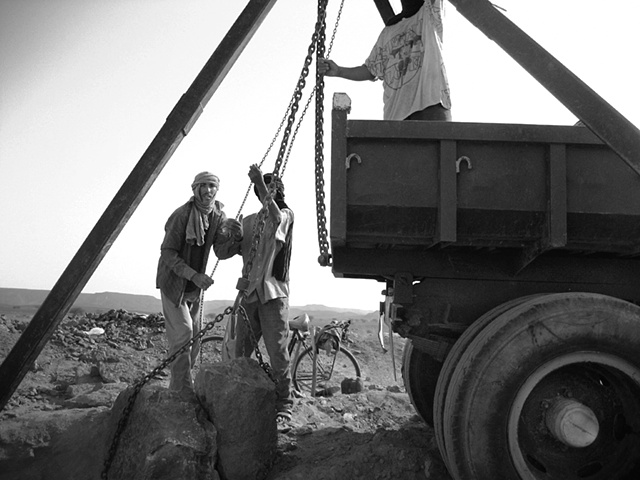 Block and tackle helps men load raw cut blocks of limestone containing the crystal darts of squid skeletons.