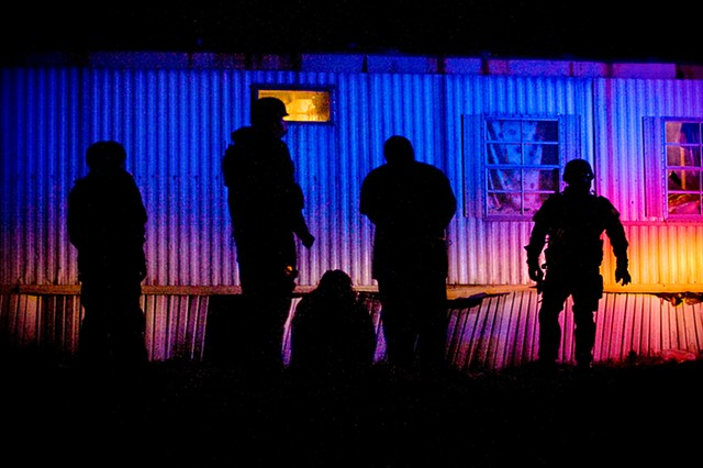 Officers stand watch over a pair of detained men after a police raid on a home suspected of drug trafficking on Jan. 6, 2010 in Wade, North Carolina.