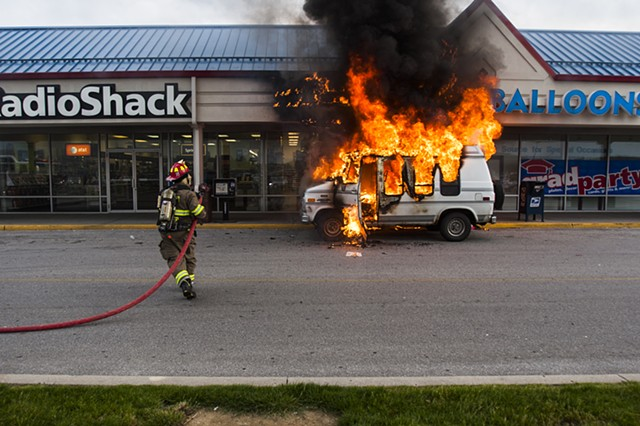 A firefighter rushes to extinguish a car fire, May 14, 2009, Hanover, Pa.