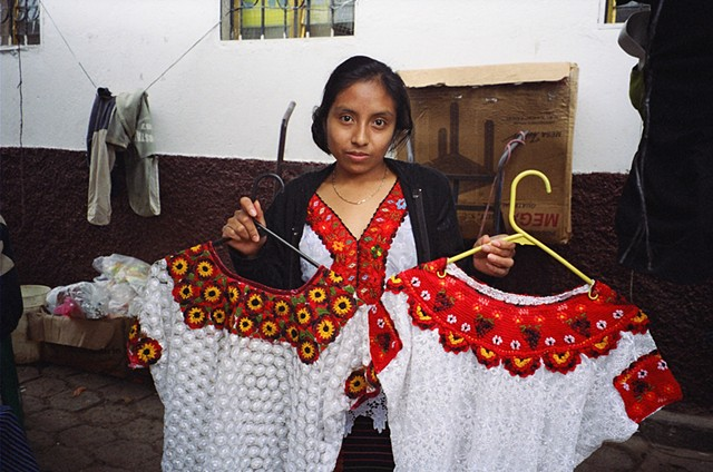 A woman selling mass produced huipils (blouses) in the Colotenango market, 2010