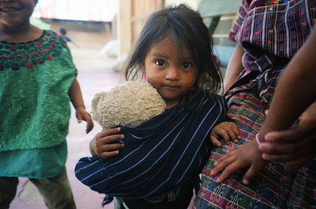Child in Santa Elena village, with teddy bear carried in a traditional woven sling, 2011