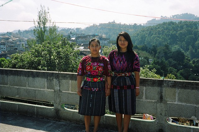 Young women in Chichicastenango modeling their fashionable traditional dress - the short corte skirts possibly stem from tourism influence.  Chichi is one of the largest textiles markets, shoppers are predominantly tourists traveling in and out on the sam