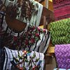 Huipil (blouse) display in Santiago Atitlan market.  On the left are pricey embroidered huipils, on the right, more economical blouses.