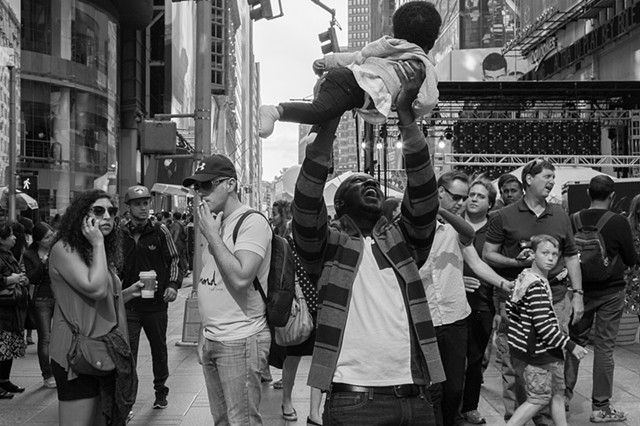 Photograph of a father holding up his child in joy, Times Square, NY, Manhattan, by Judith Ebenstein