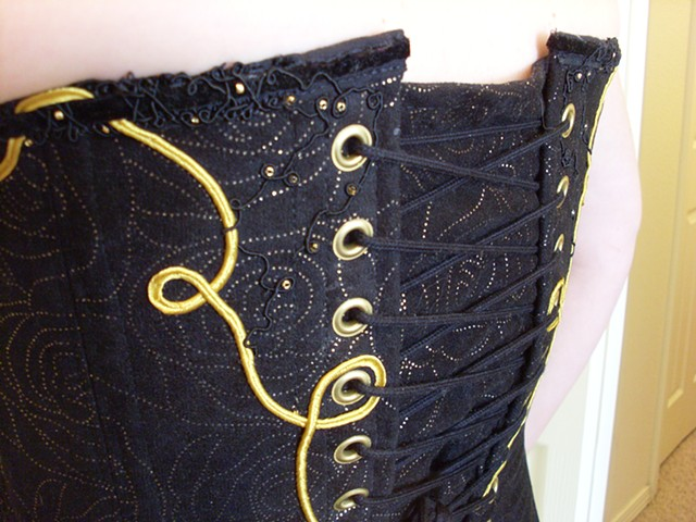 french embroidery in the back of a black and gold corset