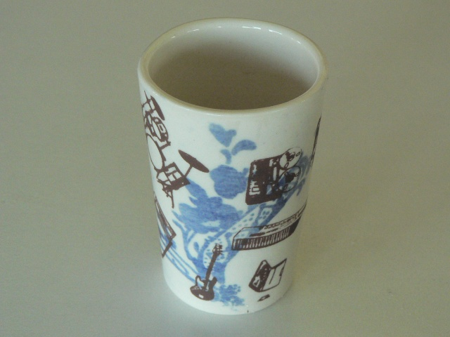 porcelain Shotglass Slipcast from handmade molds, decorated with photosensitive glaze and screen printed overglaze decals of guitars and drums
