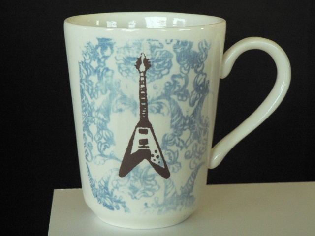 porcelain mug Slipcast from handmade molds, decorated with photosensitive glaze and screen printed overglaze decals of a flying v guitar on damask