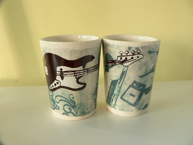 porcelain Shotglass Slipcast from handmade molds, decorated with photosensitive glaze and screen printed overglaze decals of guitars