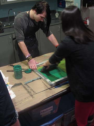 High School Intern Dylan printing with a museum visitor
