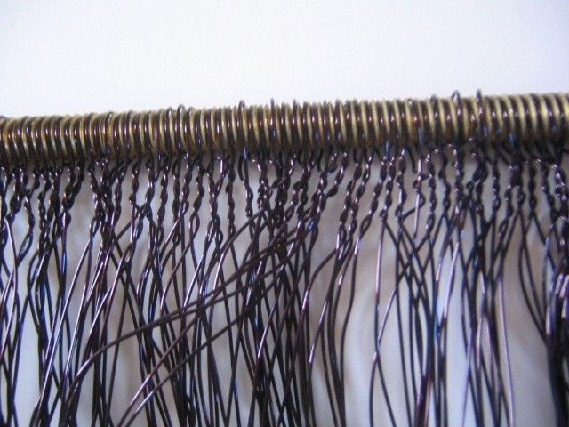 Detail of wire art work twisted in various ways to create a wall piece