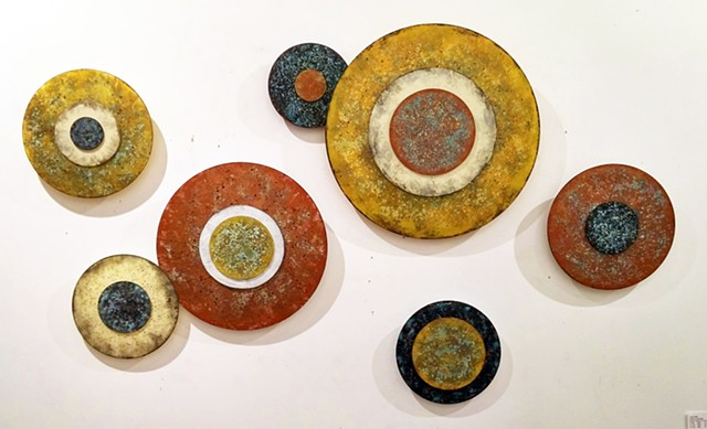 Circular art installation wall sculpture of elevated disk paintings in an earthy palette.